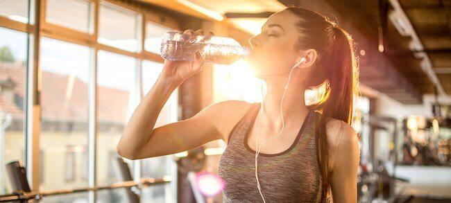 Ragazza in palestra che beve acqua da una bottiglietta