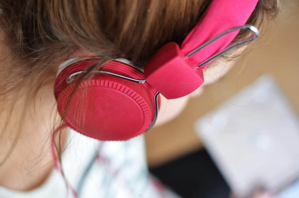 Una ragazza che ascolta la musica con cuffie rosa per l'articolo come utilizzare lo smartphone nel fitness