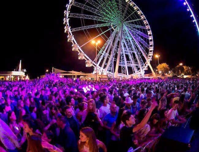 Una folla di persone che balla di sera in una piazza a Rimini