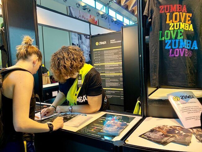 Una ZCOM volontaria di Zumba Fitness che offre informazioni ai visitatori del padiglione