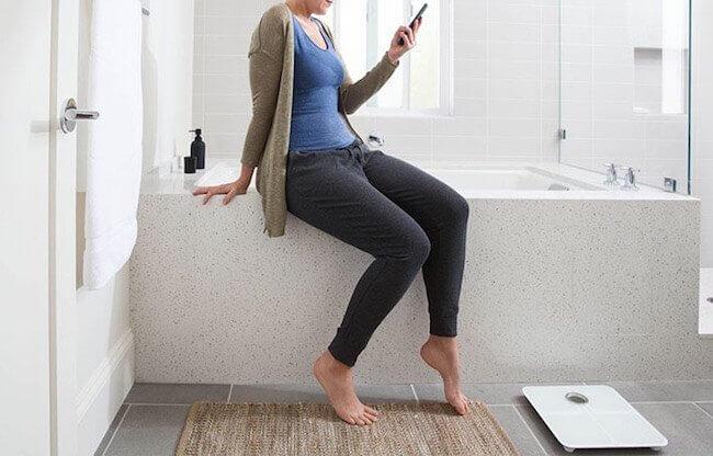 Una ragazza in bagno che sta per salire sulla bilancia fitbit Aria