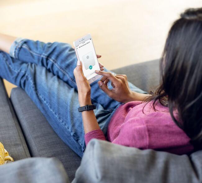 Una ragazza sul divano che sta configurando la bilancia fitbit Aria