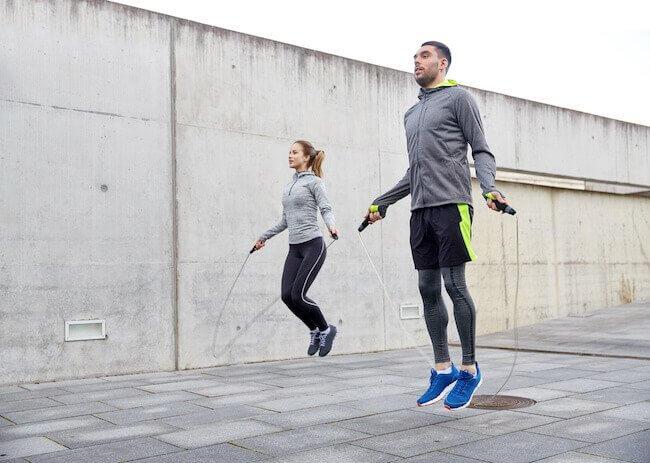 Un uomo ed una donna che stanno saltando la corda