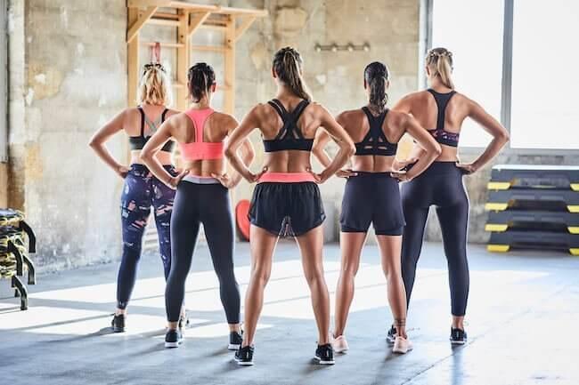 Cinque ragazze girate di spalle vestite con abbigliamento sportivo adatto ai corsi fitness