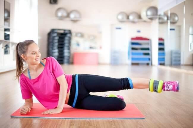 Una ragazza con una maglia larga rosa che sta facendo alcuni esercizi a terra in sala pesi