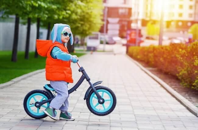 Bambino piccolo sulla bicicletta senza pedali