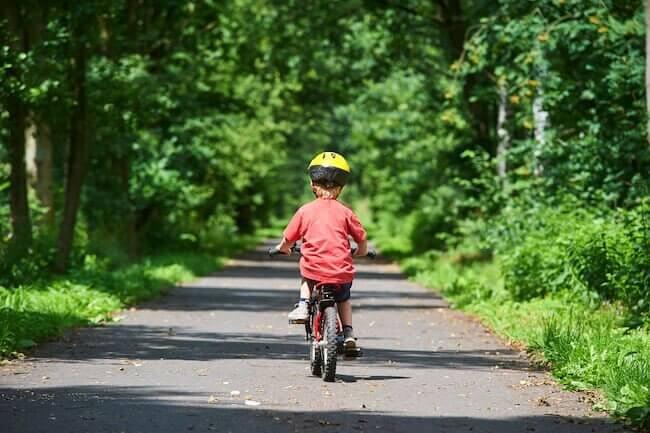 Bambino con un casco giallo che sta guidando una bicicletta