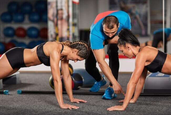 Personal trainer che allena due ragazze in palestra