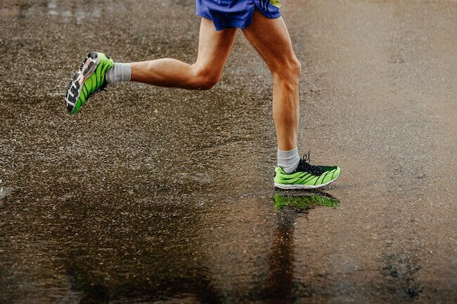 Gambe di un uomo che corre su di una strada asfaltata