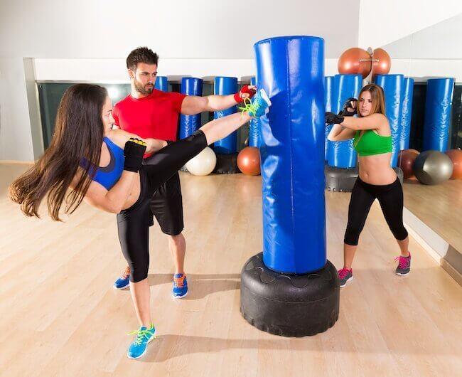Due allieve che si esercitano contro un sacco da fit boxe insieme al loro istruttore