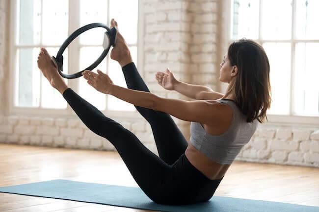 Una ragazza che si sta allenando con pilates matwork ed utilizza un anello come piccolo attrezzo