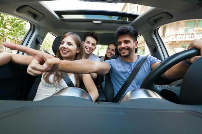 Quattro amici in macchina che stanno cercando un parcheggio in palestra