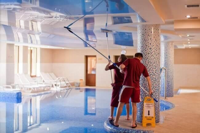 Due addetti alle pulizie che stanno pulendo il tetto di una piscina in palestra