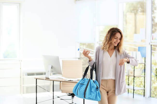 Una ragazza che sta uscendo dal suo ufficio guardando che ore sono per andare in palestra