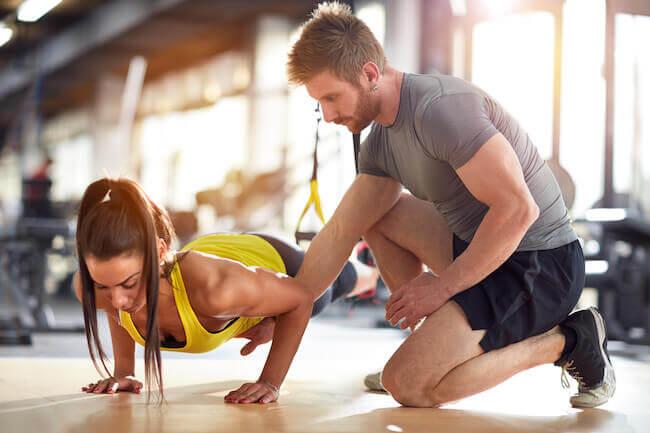 Personal trainer che sta allenando un cliente