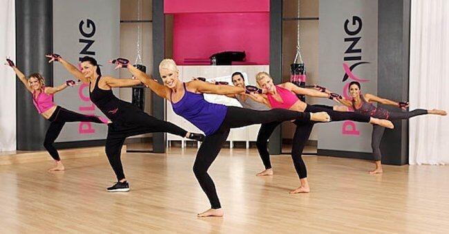 Ragazze che effettuano un movimento di pilates durante una lezione di Piloxing