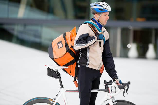 Uomo in bicicletta con un borsone sportivo di colore arancione alle spalle