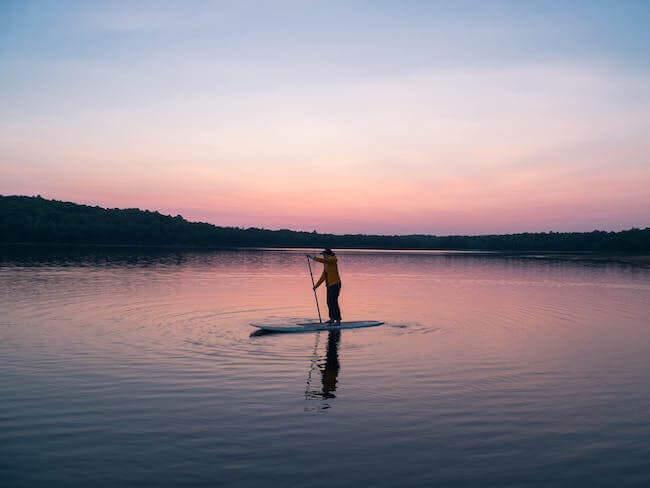 Un uomo che sta pagaiando su un lago al tramonto