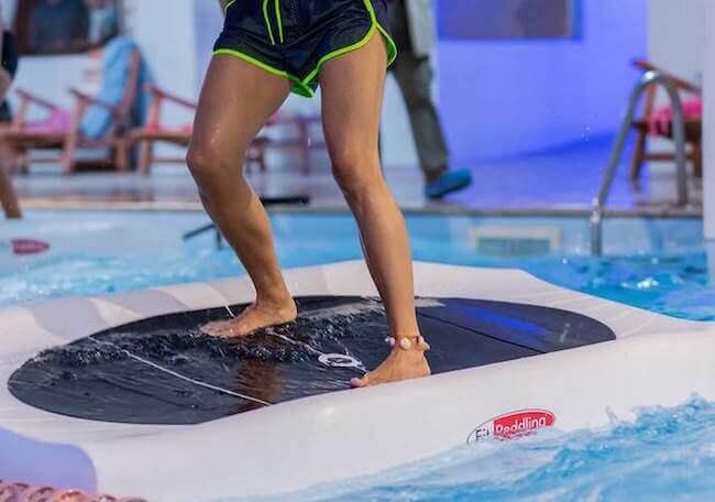 Un ragazzo che sta facendo SUP in piscina