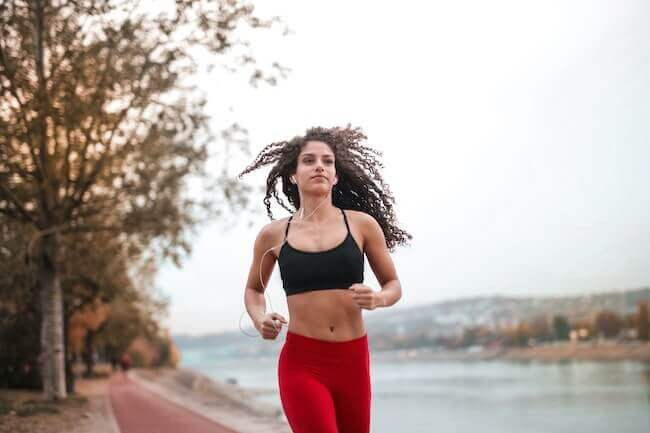 Una ragazza in leggings rossi e top nero che corre nel parco fluviale