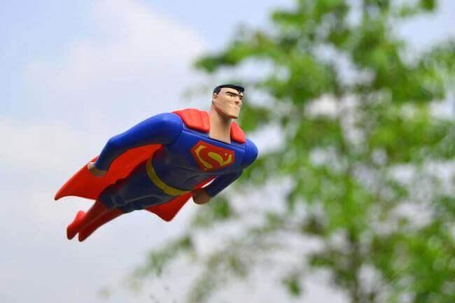 Un giocattolo di Superman che sta volando in un giardino