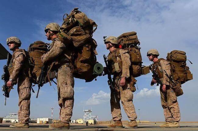 Quattro marine americani con grossi zaini in spalla