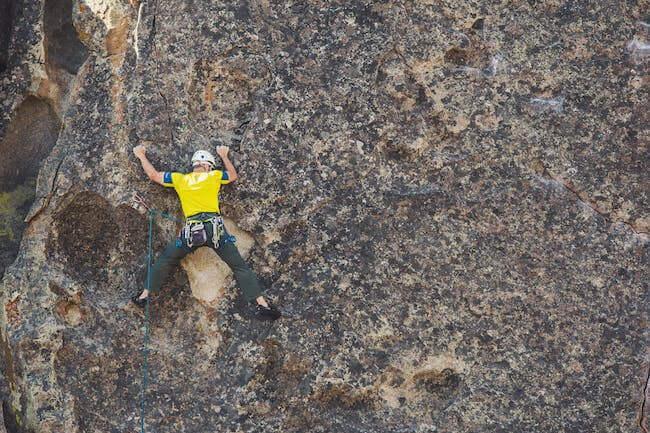Un uomo che sta facendo una arrampicata in montagna in sicurezza