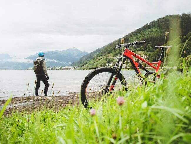 Un ragazzo sulla riva di un lago di montagna con la sua bicicletta
