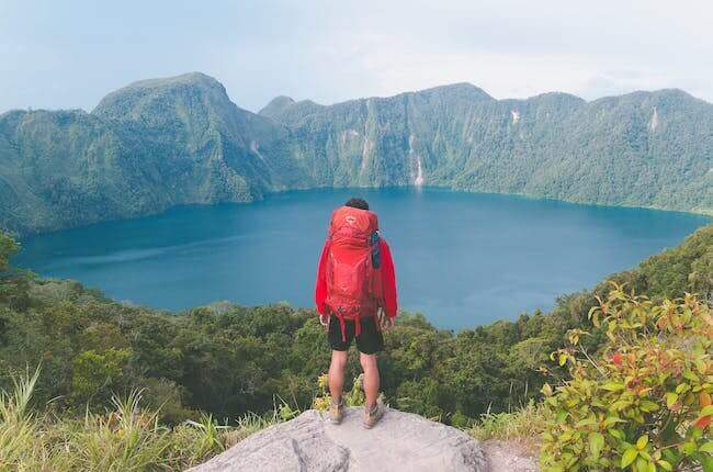 Un uomo attrezzato per trekking in montagna che si trova davanti ad un bellissimo lago