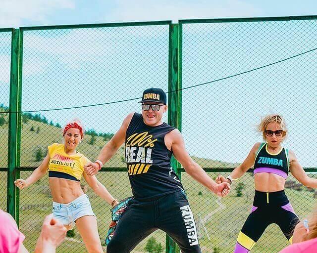 Un presenter con due ragazze che stanno facendo Zumba fitness