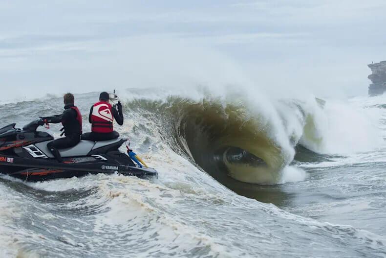 Un surfista che viene ripreso da un cameraman su una moto d'acqua