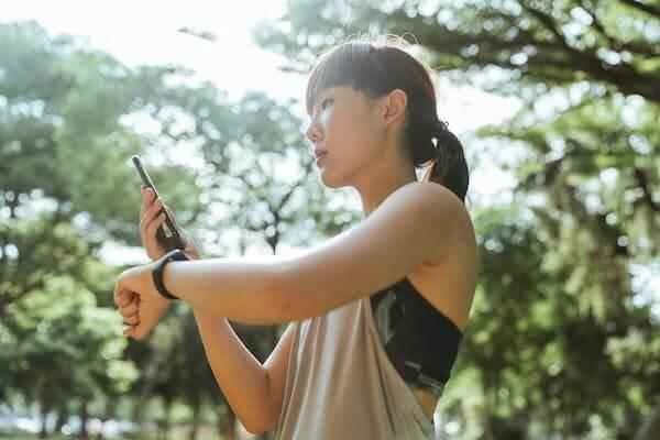 Una ragazza nel parco che si prepara a fare running seguita dal suo coach online tramite videochiamata