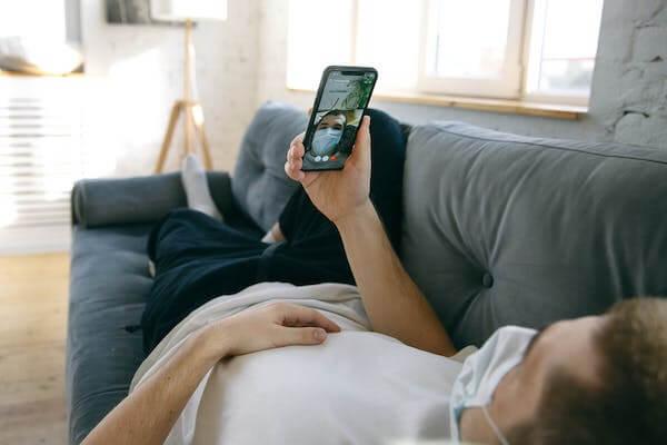 Un ragazzo sdraiato sul divano di casa che sta videochiamando il suo coach