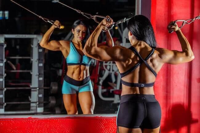 Una donna molto muscolosa che si sta specchiando in palestra