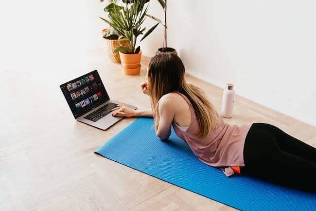 Una ragazza sdraiata sul tappetino fitness in casa, di fronte al portatile, pronta per allenarsi