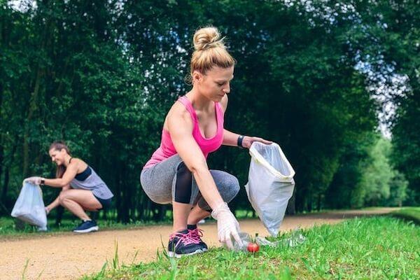 Due ragazze che stanno facendo ploggin al parco mentre raccolgono rifiuti da un giardino pubblico