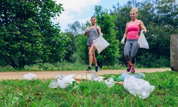 Due ragazze che stanno correndo incontro ad alcuni rifiuti in un giardino pubblico