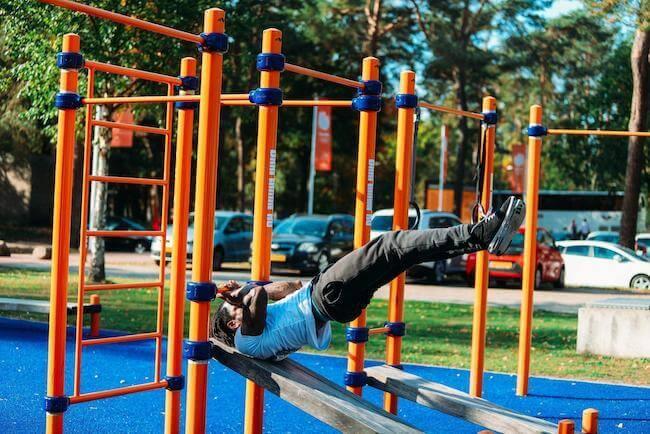 Un ragazzo che si sta allenando facendo trazioni sulla sbarra di un parco