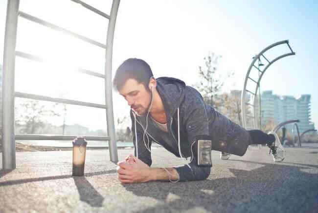 Un ragazzo che sta facendo un plank sopra un ponte della città