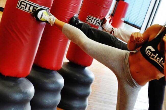 Una lezione di Fit Boxe in palestra, nel dettaglio una ragazza che sta tirando un calcio contro il sacco rosso