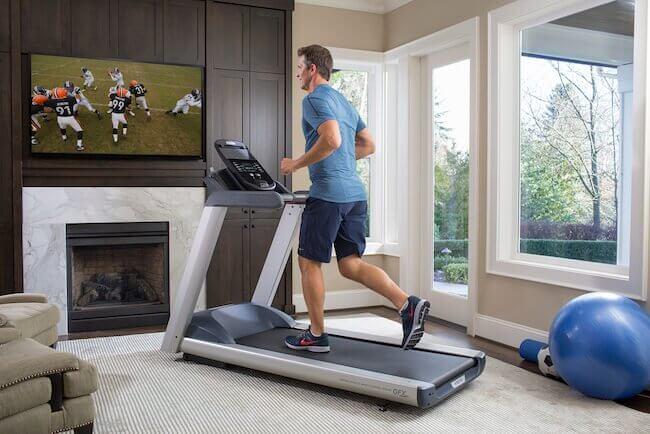 Un uomo che si sta allenando nel soggiorno con il proprio tapis roulant mentre sta guardando la tv